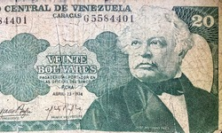 A close-up macro photo of a worn Venezuelan banknote of 20 bolivares printed in 1974. The banknote features a portrait of president of the republic in the 19th century Jose Antonio Paez.