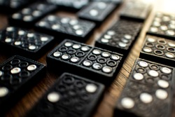 A close up, macro shot of a Domino piece, in the middle of others in a pattern. Dominoes is a family board game where one connects and links the pieces together to win.
