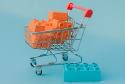 A close-up, mini supermarket cart filled with orange bricks against a blue background. Idea - color contrast, purchase of children's educational toys, construction.