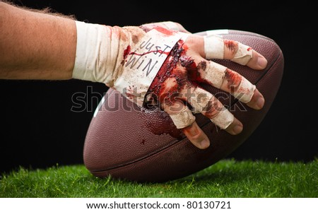 A close up of a beat up hand about to hike a football.