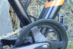 A close up of a bicycle chain and a black crank shield, and an  aluminum frame is blurred in background