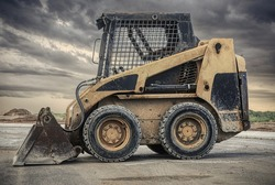a close up of a bobcat or a skid steer loader used in construction,landscaping and agriculture. It has a many purpose bucket in the front.