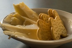 A close-up of a bowl of butterfly shaped crackers with carved slices of sharp cheddar cheese