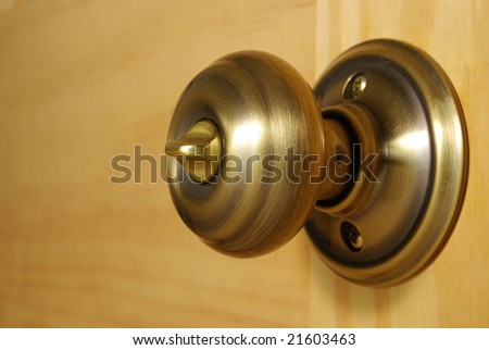 A close-up of a brass doorknob on a pine wood door.