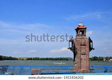 A close up of a brick structure or pole with two metal light handling boxes next to a blue railing and with a boat swiming along a vast river or lake in the background and some trees below the horizon #1451836202