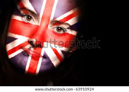 A close up of a british flag on a female face over dark background