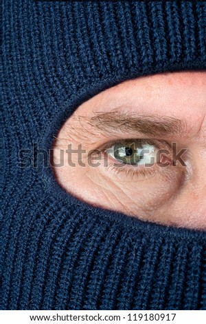 A close up of a burglar peering through a blue ski mask to hide his identity.
