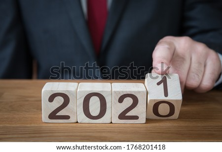 Photo of  A close up of a businessman looking ahead to the future with confidence and changing the date of a calendar to 2021
