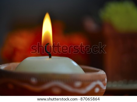A close up of a candle in a terra-cotta holder