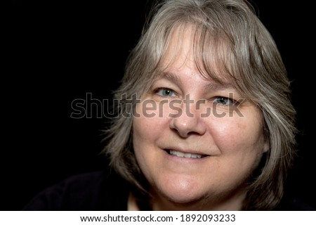 A close up of a Caucasian female in late forties to early fifties. She is smiling with a black background with room for text. Stock photo ©