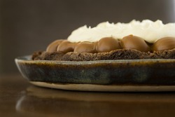 A close up of a chocolate balls cake with white cream on the top on a brown reflecting surface