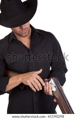 a close up of  a cowboy checking his rifle for bullets.