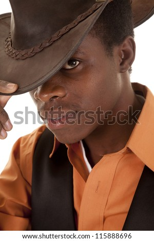 a close up of a cowboy holding on to the brim of his hat with a serious expression on his face