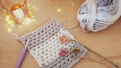 A close up of a crocheted scarf pattern in progress, made with chunky weight, self striping yarn in a neutral tone, posed with a crochet hook, dried flowers, fairy lights, and a votive candle.