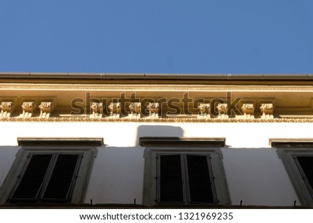 A close-up of a decorated cornice on a historical building with traditional Italian green window shades. #1321969235