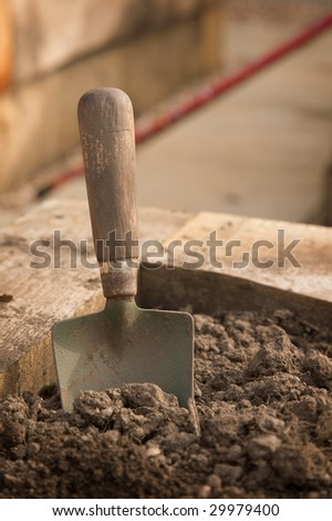 A close-up of a dirty old trowel standing in the earth