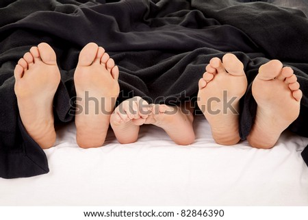 a close up of a family showing off their feet under the covers. - stock photo