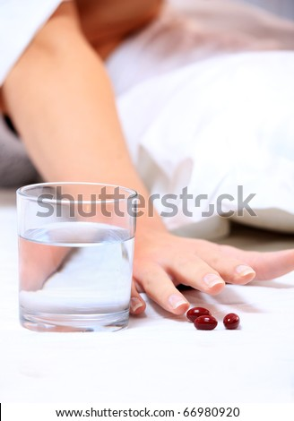 A close up of a female hand reaching for some tablets over white background
