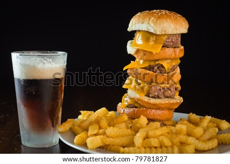 A close up of a five patty cheese burger with fries and a beer.