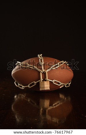 A close up of a football locked up with chain.