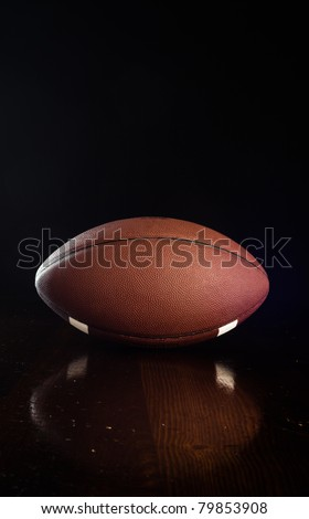 A close up of a football on a wood table.