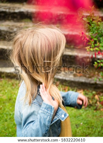 A close up of a girl looking away while adjusting her long blonde hair with her right hand. Hair blown away on a windy day. A child playing in an english garden. Distracted girl. Zdjęcia stock ©