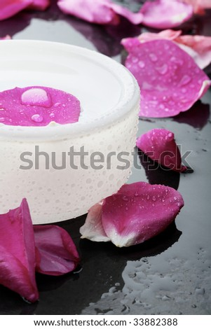 A close-up of a health and beauty spa decoration with a pink flower petal and water droplet resting on the water surface in an opaque round bowl surrounded by more pink flower petals.