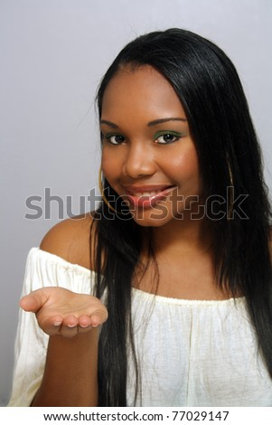 A close-up of a lovely young Haitian girl with a captivating smile and her hand toward the camera, palm up.  Slight selective focus on her hand to draw attention to whatever you place in her hand.