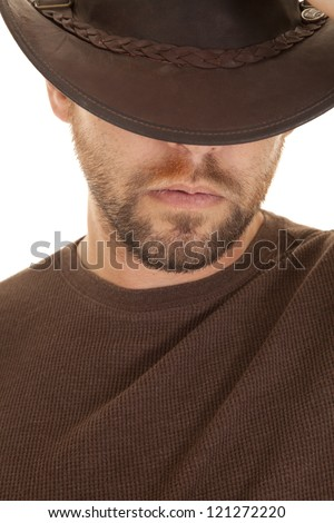 A close up of a man in his brown shirt and cowboy hat with a serious expression on his face
