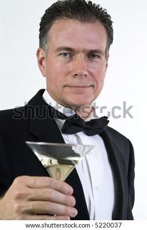 A close up of a man's hand who is dressed in formal attire and holding a martini glass.