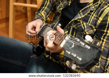 A close up of a man's hands playing the guitar.