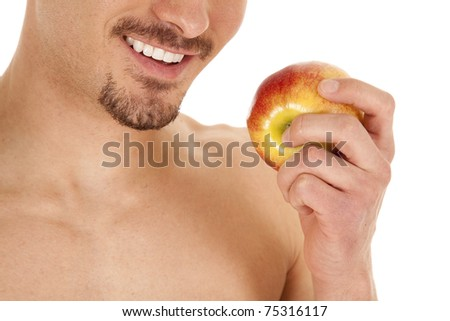 A close up of a man smiling with an apple.