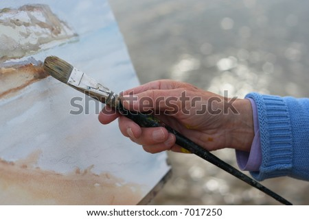 A close up of a mature artists hand painting a coastal landscape.