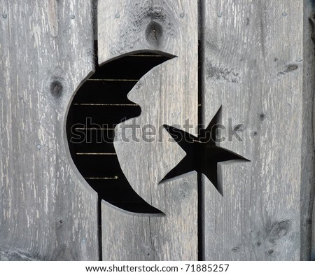 a close up of a moon and stars cut-out on a rustic weathered wooden outhouse door