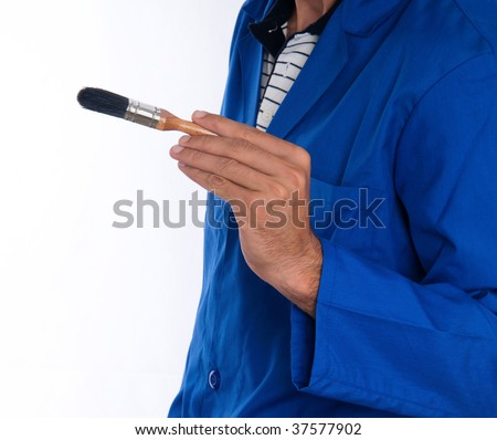 A close up of a painter wearing a blue jumpsuit with a black bristled brush in his right hand.