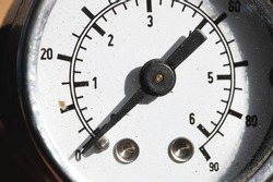 A close-up of a part of the white dial of an old manometer with an arrow at zero. Production stop and malfunction concept