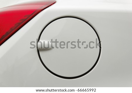 A close up of a petrol cap cover on a modern white car