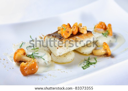 A close-up of a portion of fish with chanterelle mushrooms served with sauce on a white plate