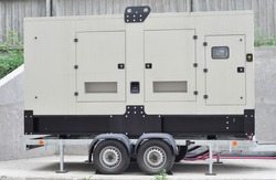 A close-up of a quiet towable, standalone emergency gaseous generator. A mobile trailer mounted natural gas generator is providing transportable power to the construction, industrial applications.