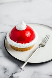 A close-up of a red and white mousse tartelette dessert on a white plate, a dessert fork, marble background. Light, bright, airy photo