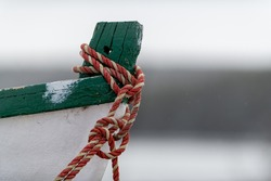 A close-up of a red, blue and white fishing rope wrapped around the bow of a white boat with green trim.  The bow of the fishing boat is made of wood and it moored at a dock.