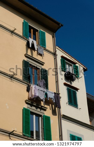 A close up of a residential building in Florence, Italy, with clothes drying out in the sun from windows with traditional green window shades #1321974797