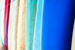 A close up of a row of colourful surfboards lined up at a seaside shack ready to be rented to a local surfer at the beach