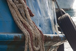 A close up of a rusty old rope and two black wheels hanged with an old broken old blue car