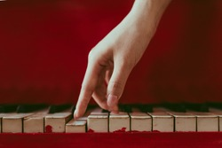 a close-up of a side view with female hand with pink manicure playing the piano. An old red piano with black and white keys. A palm above the keyboard. Graceful fingers of composer or musician