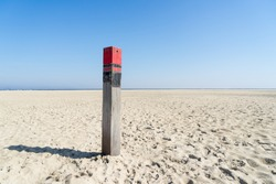 A Close up of a single red beach pole or column on an empty beach at the Dutch North Sea in summer with blue sky