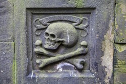 A close-up of a skull and crossbones on a headstone in a graveyard.