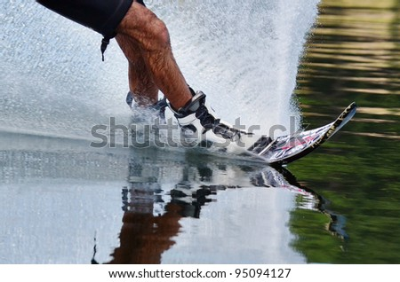 A close up of a slalom water skiers legs and skis with water splash.