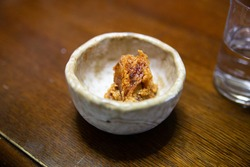 A close-up of a small Japanese side dish made of miso in an old stone made bowl on a wooden dining table