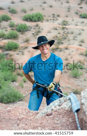 A close up of a smiling rock climber getting ready to rappell down a mountain after a climb up a steep slope.